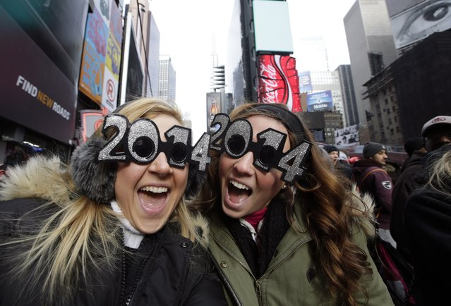 Veronica Boshen and Brittany Wells, of Allentown, Pa., pose for a photo with their 2014 glasses while waiting for the celebration to begin in Times Square on New Year's Eve, Tuesday, December 31, 2013, in New York. (Photo by Kathy Willens/AP Photo)