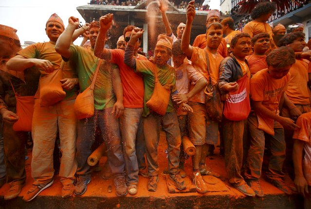 Devotees celebrate Sindoor Jatra vermillion powder festival at Thimi, in Bhaktapur April 15, 2015. The festival is celebrated by singing, dancing, playing traditional instruments, carrying chariots of various deities around the town, offering prayers and throwing vermilion powder over each other to mark the Nepalese New Year and the beginning of the spring season in the country. (Photo by Navesh Chitrakar/Reuters)