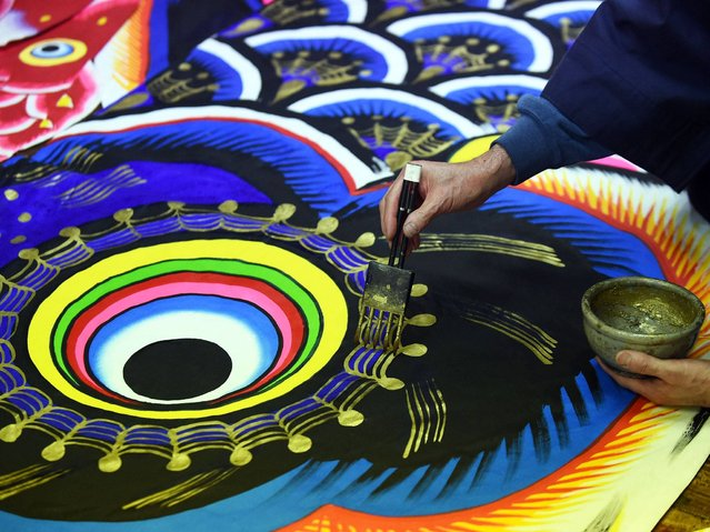Masaru Hashimoto puts gold paint onto a carp streamer at a factory in Kazo, Saitama prefecture, some 50-kilometre north of Tokyo on April 15, 2015. (Photo by Toshifumi Kitamura/AFP Photo)