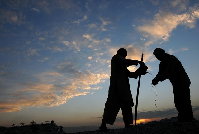 An Afghan farmer, left, pours water for his colleague to wash his hand after finishing work in Mazar-i Sharif, capital of Balkh, north of Kabul, Afghanistan on Monday, April 6, 2015. (Photo by Mustafa Najafizada/AP Photo)