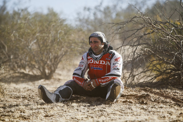 Honda rider Paulo Goncalves of Portugal weeps as he sees his motorcycle on fire during the fifth stage of the Dakar Rally between the cities of Chilecito and San Miguel de Tucuman, Argentina, Thursday, January 9, 2014. (Photo by Victor R. Caivano/AP Photo)