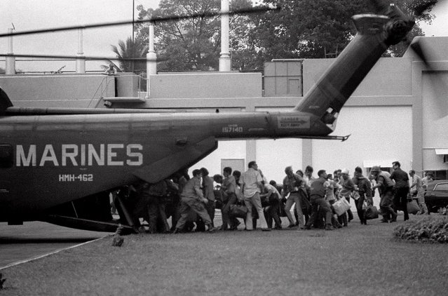 Authorized U.S. military and civilian personnel rush to board a Marine helicopter during the evacuation of the U.S. Embassy in Saigon, April 29, 1975. (Photo by Neal Ulevich/AP Photo)