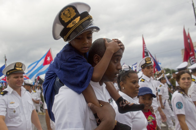 A Cuban Navy soldier carries a child on his shoulders as they march in Revolution Square marking May Day, in Havana, Cuba, Friday, May 1, 2015. Thousands of people converged on the plaza for the traditional march, led this year by President Raul Castro and Venezuelan President Nicolas Maduro. (Photo by Ramon Espinosa/AP Photo)