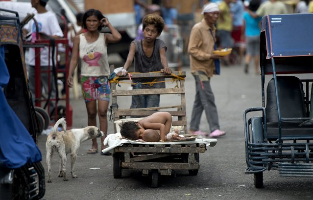 A boy pushes a wooden cart with his siblings on it at a market in Manila on April 24, 2015. (Photo by Noel Celis/AFP Photo)