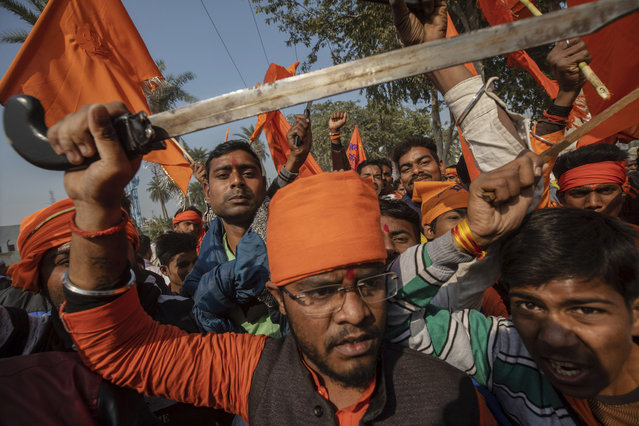 In this Sunday, November 25, 2018 photo, Hindu hardliners, one holding a sword, chant slogans against Muslim communities during a rally demanding a Hindu temple be built on a site in northern India where hardliners in 1992 had attacked and demolished a 16th century mosque in Ayodhya Uttar Pradesh. Riots had left about 2,000 people dead. (Photo by Bernat Armangue/AP Photo)