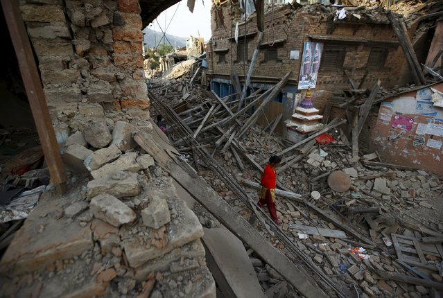 A woman walks along a street near collapsed houses after the April 25 earthquake at Sankhu, on the outskirts of Kathmandu May 6, 2015. (Photo by Navesh Chitrakar/Reuters)