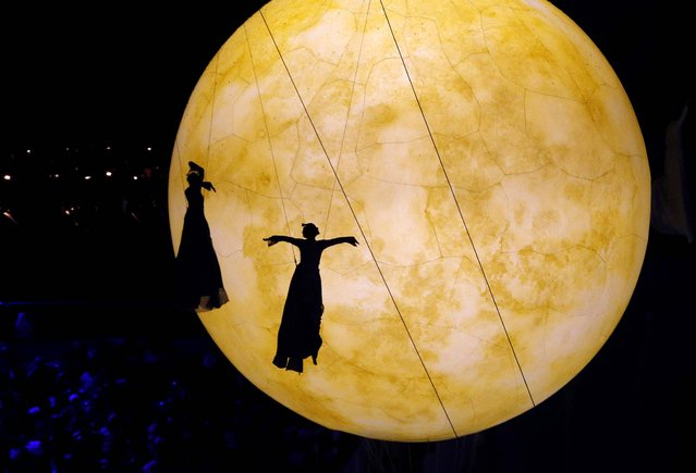 The shadow of artists fall on a giant balloon meant to represent the moon. (Photo by Dmitry Lovetsky/Associated Press)