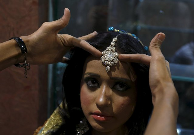 A model is being helped to adjust her jewelry while she waits backstage during a self grooming bridal beauty workshop at a local mall in Karachi, Pakistan, March 22, 2016. (Photo by Akhtar Soomro/Reuters)