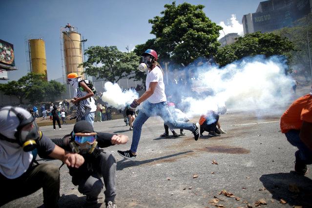 """Opposition demonstrators take cover from tear gas on a street near the Generalisimo Francisco de Miranda Airbase """"La Carlota"""", in Caracas, Venezuela April 30, 2019. (Photo by Ueslei Marcelino/Reuters)"""