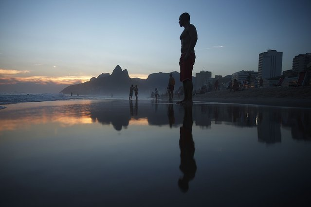 """People gather on Ipanema Beach following a """"bloco"""" street party during pre-Carnival festivities on February 23, 2014 in Rio de Janeiro, Brazil. Carnival officially begins on February 28 but pre-festivities have already begun. Brazil is gearing up to host the 2014 FIFA World Cup. (Photo by Mario Tama/Getty Images)"""