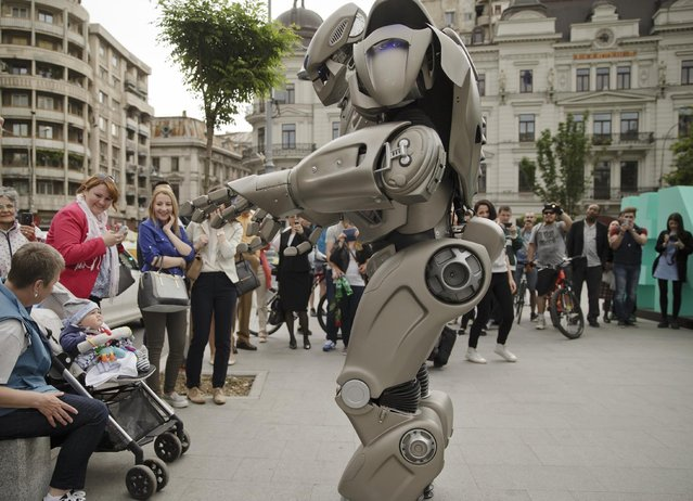A child looks up at Titan the Robot performing in Bucharest, Romania, Monday, May 11, 2015. Titan the robot is produced by British company Cyberstein Robots Ltd and gained world recognition in pop videos dancing alongside artists such as Rihanna in music videos. (Photo by Vadim Ghirda/AP Photo)