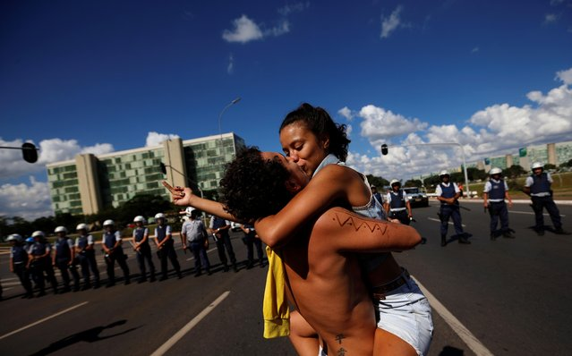 University students kiss as they protest against cuts to federal spending on higher education in Brasilia, Brazil, Wednesday, May 15, 2019. (Photo by Adriano Machado/Reuters)