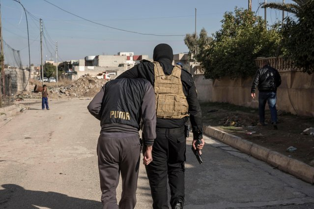 In this Tuesday, February 21, 2017 photo, an Iraqi security officer holds an Islamic State group suspect after arresting him, in eastern Mosul, Iraq. Suspects are identified via intelligence gathered from information received from other civilians in the city. (Photo by John Beck/AP Photo)
