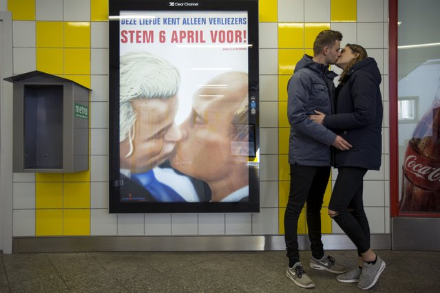 A couple stands next to a poster depicting Dutch politician Geert Wilders and Russian President Vladimir Putin kissing, at a metro station in Amsterdam April 3, 2016. (Photo by Cris Toala Olivares/Reuters)