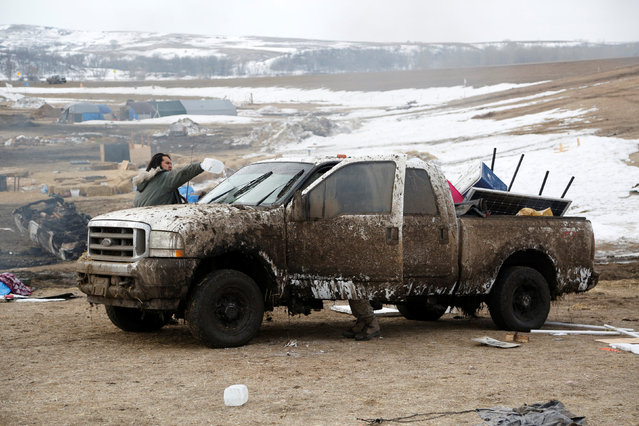 A protester washes mud from his truck before evacuating the opposition camp against the Dakota Access oil pipeline near Cannon Ball, North Dakota, U.S., February 23, 2017. (Photo by Terray Sylvester/Reuters)