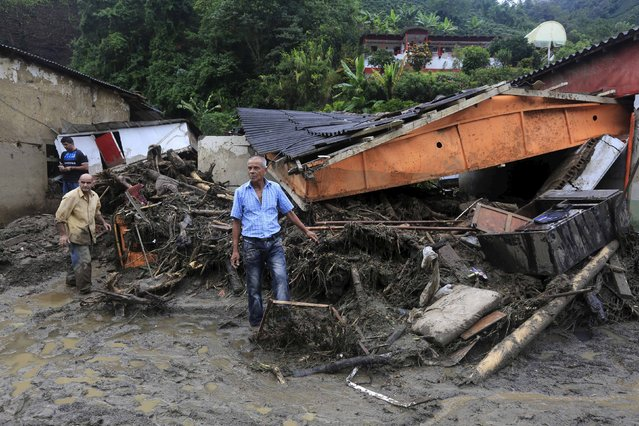 Residents stand in front their damaged house, after a landslide sent mud and water crashing onto homes close to the municipality of Salgar in Antioquia department, Colombia May 19, 2015. (Photo by Jose Miguel Gomez/Reuters)