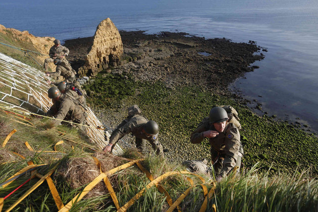 Soldiers from the U.S. 75th Ranger Regiment, in period dress, climb the cliff of Pointe-du-Hoc in Cricqueville-en-Bessin, Normandy, France, Wednesday, June 5, 2019. During the American assault of Omaha and Utah beaches on June 6, 1944, U.S. Army Rangers scaled the 100-foot cliffs to seize German artillery pieces that could have fired on the American landing troops. (Photo by Thibault Camus/AP Photo)