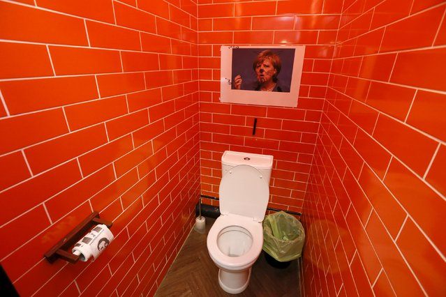 "A photo of German Chancellor Angela Merkel, which customers drew on, is seen in a toilet at the ""President Cafe"" in Krasnoyarsk, Siberia, Russia, April 7, 2016. (Photo by Ilya Naymushin/Reuters)"