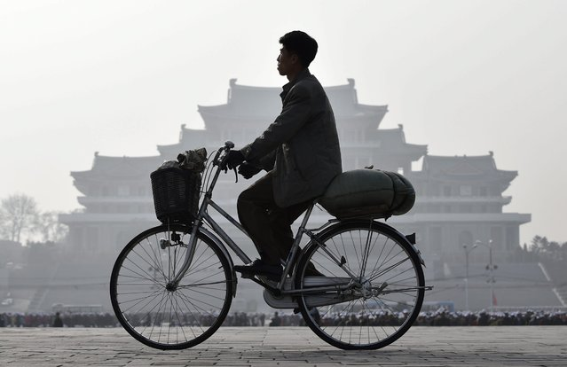 "Picture taken 13 April 2016 and made available 14 April 2016 shows a man cycling past the Kim Il Sung square ahead of the ""Day of the Sun"" celebrations in Pyongyang, North Korea. (Photo by Franck Robichon/EPA)"