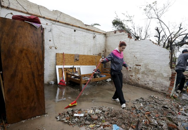 A woman clears debris from a roofless house in Dolores, the day after the city was hit by a tornado, April 16, 2016. (Photo by Andres Stapff/Reuters)