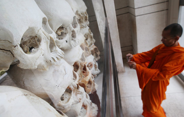 A Cambodian Buddhist monk takes pictures of the remains of victims who died during the Khmer Rouge regime at Choeung Ek Genocidal Center on the outskirts of Phnom Penh, Cambodia, 17 April 2016. Cambodians marked the anniversary of the Khmer Rouge's taking of Phnom Penh which plunged the nation into one of the worst genocides of the last century. (Photo by Mak Remissa/EPA)