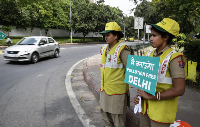 Volunteers remind commuters the reason for restriction placed on vehicle movement in New Delhi, India, Friday, April 15, 2016. The New Delhi government has begun a second round of a two-week car restriction whereby private cars will be allowed on the streets on alternate days from Friday until April 30 based on even or odd license plate numbers, to reduce air pollution that has made the Indian capital the world's most polluted city. (Photo by Saurabh Das/AP Photo)
