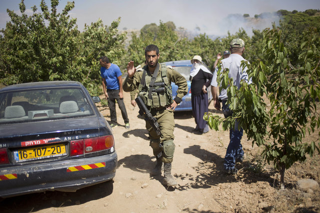 An Israeli soldiers asks from members of Israel's Druze minority to leave their cherry plantation in the Israeli controlled Golan Heights during fighting between forces loyal to Syrian President Bashar Assad and rebels in the Druze village of Khader in Syria, Tuesday, June 16, 2015. As many as 20 members of the Druze minority sect were killed last week, the deadliest violence against the Druze since Syria's conflict started in March 2011, sparking fears of a massacre against the sect. (AP Photo/Ariel Schalit)