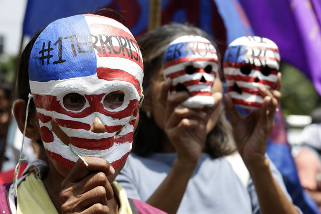 Filipino activists hold paper mache skulls  painted with US flags as they march outside the US embassy in Manila, Philippines, April 7, 2014 in a rally condemning the upcoming visit of US President Barack Obama to the country. Activists also called for an end to the presence of US troops in the country and the Visiting Forces Agreement (VFA). (Photo by Dennis M. Sabangan/EPA)
