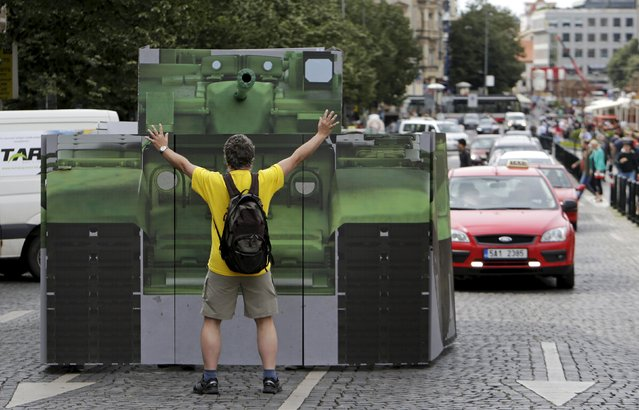 "A man symbolically tries to stop a mock Russian military tank during a performance ""Occupation Reminder"" organized by human rights activist group ""People in Need"" (PIN) in Prague, Czech Republic, June 25, 2015. The performance commemorates victims of the Soviet Union-led occupation of former Czechoslovakia and annexation of Crimea by the Russian Federation. (Photo by David W. Cerny/Reuters)"