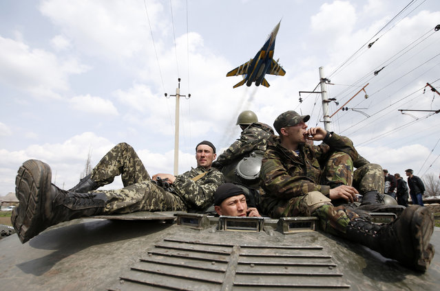 A fighter jet flies above as Ukrainian soldiers sit on an armoured personnel carrier in Kramatorsk, in eastern Ukraine April 16, 2014. Ukrainian government forces and separatist pro-Russian militia staged rival shows of force in eastern Ukraine on Wednesday amid escalating rhetoric on the eve of crucial four-power talks in Geneva on the former Soviet country's future. (Photo by Marko Djurica/Reuters)