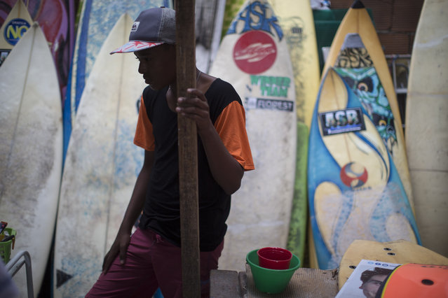 Robert Silva watches as boards are repaired at the Rocinha Surf Association headquarters in the Rocinha slum in Rio de Janeiro, Brazil, Thursday, July 2, 2015. Along with free surf boards and clothes, kids are taught how to maintain and fix their gear. (Photo by Felipe Dana/AP Photo)