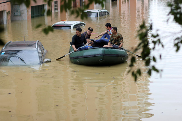 People row in a rubber dinghy in a flooded neighborhood after heavy rainfall in Yongzhou, Hunan Province, China, May 5, 2016. (Photo by Reuters/Stringer)