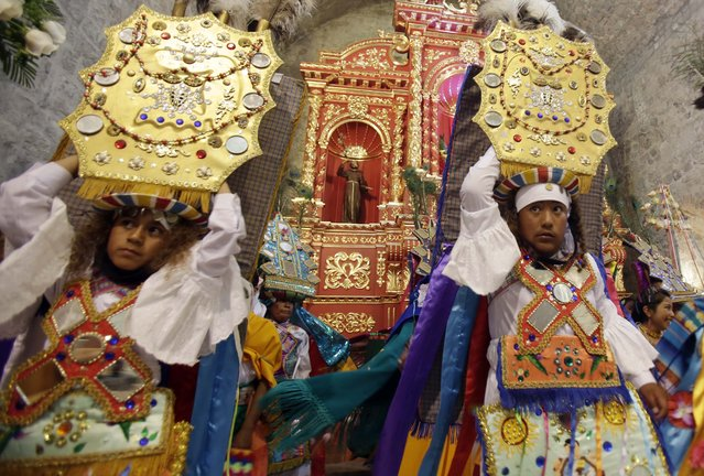 In this June 4, 2015 photo, a group of dancers perform on the main altar of the Catholic church in Pujili, Ecuador, showing gratitude to the Inca Sun God, Inti, the harvest, as well as celebrating the Holy Communion. While most of the region's native peoples identify themselves as Roman Catholic, some practice syncretic rituals that blend the church's traditional beliefs with native customs. Many Andean people see no contradiction in it. (Photo by Dolores Ochoa/AP Photo)