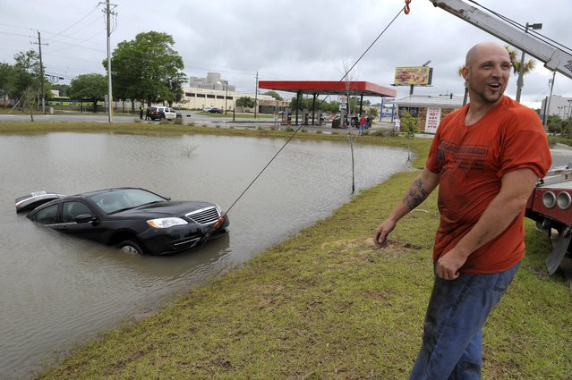 Michael Harrell of J&J Towing smiles as a tow truck operated by coworker Charles Thomas pulls a flooded car that was swept off Fairfield Avenue by torrential rains and deposited in a ditch in Pensacola, Fla., Wednesday, April 30, 2014. Heavy rains and flooding have left people stranded in houses and cars in the Florida Panhandle and along the Alabama coast. (Photo by G.M. Andrews/AP Photo)