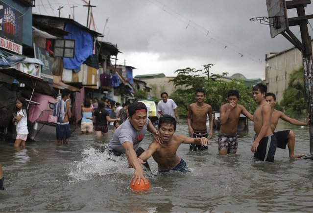 Filipino boys scramble for a ball possession as they play basketball in floodwaters from a swollen creek at a coastal village in Malabon, north of Manila, Philippines, Wednesday, July 8, 2015. (Photo by Aaron Favila/AP Photo)