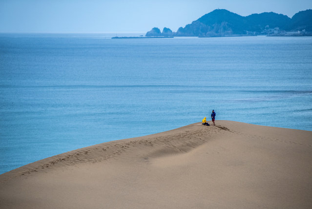 People visit Tottori Sand Dunes on August 27, 2019 in Tottori, Japan. The Tottori Sand Dunes form the only large dune system in Japan and were created by sediment deposits carried by the Sendai River into the Sea of Japan. Sea currents and wind brought the sand from the sea floor to the shore, where the wind constantly rearranges the shape. The dunes have existed for over 100,000 years but are now decreasing due to a post-war government reforestation program and concrete barriers erected to protect the coast from tsunamis which have disrupted the currents responsible for bringing the sand to shore. Although authorities have begun measures to protect the dunes, including dumping sand off the shore in the hope that it will wash ashore, as well as employing the manual removal of encroaching grassy areas, the result is as yet unclear. (Photo by Carl Court/Getty Images)