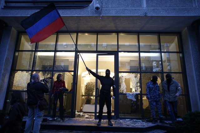 A pro-Russia protester waves a Donbass flag as they storm the governor's business premises in Donetsk, eastern Ukraine May 3, 2014. (Photo by Marko Djurica/Reuters)