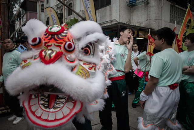 "A participant takes part in a lion dance during the ""Bun Festival"" on the island of Cheung Chau in Hong Kong on May 6, 2014. The traditional ""Bun Festival"" is held every year to placate the hungry ghosts of old pirates. Legend has it that buns bring good luck to the island's fisherman protecting them from the spirits of pirates that once lurked in the region. (Photo by Philippe Lopez/AFP Photo)"