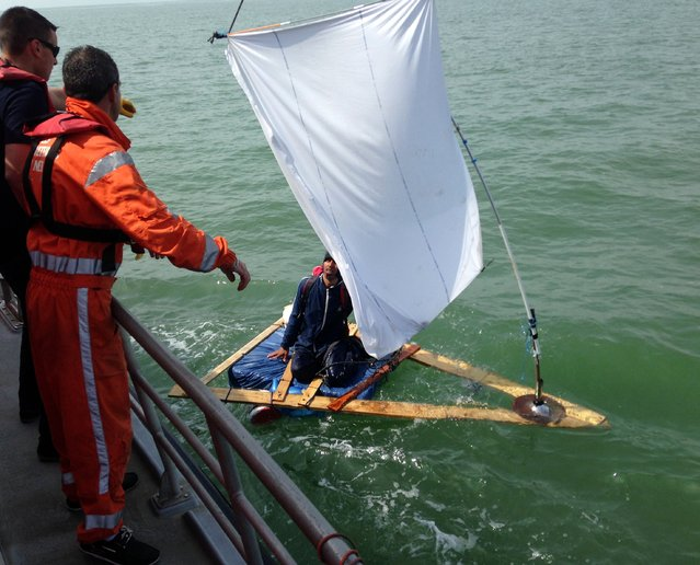 "French coast rescuers support a 23-year-old Afghan trying to cross the Channel on a makeshift raft using a bedsheet as a sail, on May 5, 2014 off Sangatte. The man, who had started developing hypothermia, ""was first disappointed and then glad at being rescued"", said Bernard Barron, the head of the coast rescue service in Calais. (Photo by AFP Photo/SNSM Calais)"