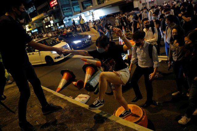 Anti-government protesters help one another cross the road after blocking it in downtown Hong Kong, October 4, 2019. (Photo by Susana Vera/Reuters)