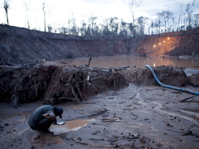 An informal miner works to separate flecks of gold from the sandy, alluvial soil, using mercury to bind inside the crater of a gold mine process in La Pampa in Peru's Madre de Dios region. (Photo by Rodrigo Abd/AP Photo)