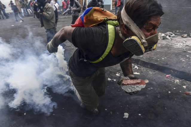 A demonstrator clashes with riot police as thousands march against Ecuadorean President Lenin Moreno's decision to slash fuel subsidies, in Quito on October 9, 2019. (Photo by Martin Bernetti/AFP Photo)
