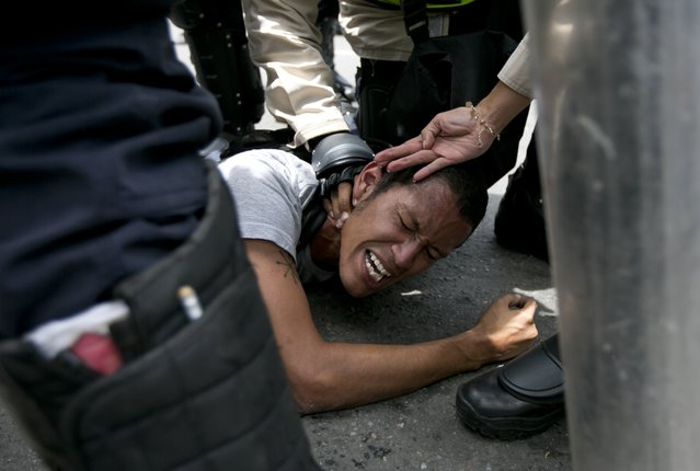An anti-government protester is detained by Bolivarian National Police during a march in Caracas, Venezuela, Wednesday, May 18, 2016. (Photo by Ariana Cubillos/AP Photo)