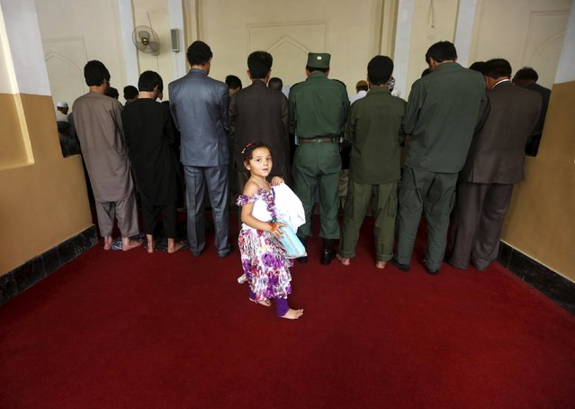 Afghans take part in morning prayers to celebrate the first day of the Muslim holiday of Eid-al-Fitr, marking the end of the holy month of Ramadan, at Eid Gah mosque in Kabul, Afghanistan July 17, 2015. (Photo by Omar Sobhani/Reuters)