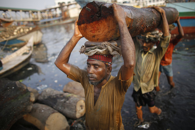 Workers carry a log at a timber factory by the river Buriganga in Dhaka May 18, 2014. (Photo by Andrew Bira/Reuters)