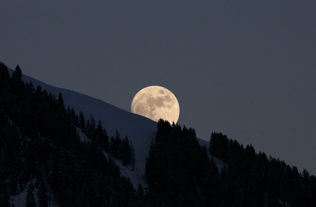 The moon rises above the trees near the Streif course in Kitzbuehel, Austria, January 22, 2016. (Photo by Leonhard Foeger/Reuters)