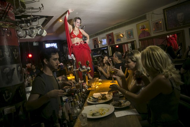A belly dancer dances on the bar at Georgian restaurant Nanuchka in Tel Aviv, Israel July 15, 2015. (Photo by Baz Ratner/Reuters)