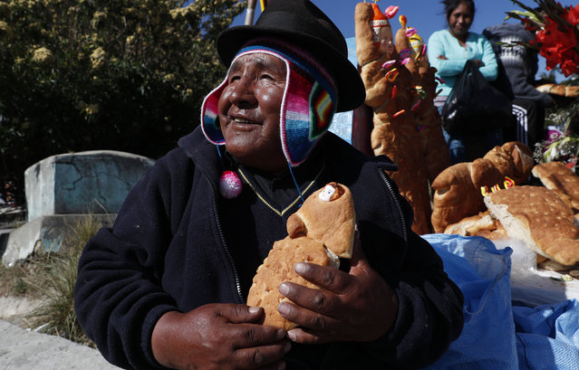 """A man holds a traditional Tantawawas, bread shaped as children, after praying at a grave of a family member during Day of the Dead celebrations at La Llamita cemetery, in La Paz, Bolivia, Saturday, November 2, 2019. In the Quechua language, which is spoken by over 2 million people in Bolivia, the word """"tanta"""" means bread and the word """"wawa"""" means baby. (Photo by Juan Karita)/AP Photo"""