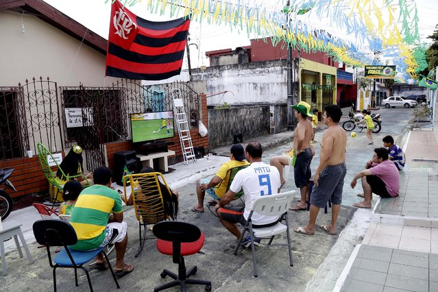 People watch the opening match in an alley in Manaus, Brazil. (Photo by Marcio Jose Sanchez/Associated Press)