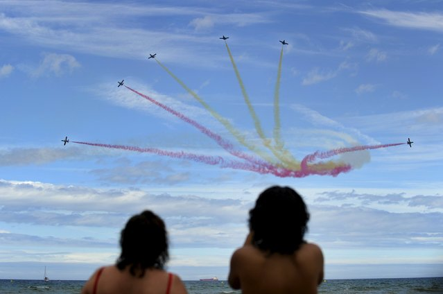 Beach-goers watch as C-101 Aviojets from the Spanish Air Force aerobatic group Patrulla Aguila fly over San Lorenzo beach during an aerial exhibition in Gijon, northern Spain, July 26, 2015. (Photo by Eloy Alonso/Reuters)